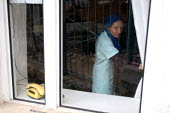 An old woman watches through the window, Azokh, Nagorno Karabakh, Azerbaidjan, March 2005. The region, although officially located within Azerbaidjan, is being occupied by Armenia and has became a de... - Boris Heger - 04-03-2005