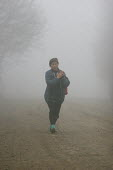 Woman walking in the mist, Azokh, Nagorno Karabakh, Azerbaidjan, March 2005. The region, although officially located within Azerbaidjan, is being occupied by Armenia and has became a de facto Republic... - Boris Heger - 04-03-2005