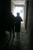 People pass by in a corridor in a delapitated residential block transformed into a displaced persons center for Georgians who used to live in Abkhazia, Zugdidi, Georgia, March 2005. The region of Abkh... - Boris Heger - 08-03-2005