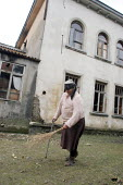 A man cleans the surroundings of an old delapitated residential block transformed into a displaced persons center for Georgians who used to live in Abkhazia, Zugdidi, Georgia, March 2005. The region o... - Boris Heger - 08-03-2005