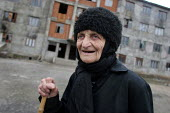 An old displaced person stands in front of a delapitated residential block transformed into a center for Georgians who used to live in Abkhazia, Zugdidi, Georgia, March 2005. The region of Abkhazia, o... - Boris Heger - 08-03-2005