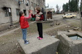 Displaced children play in front of a delapitated residential block transformed into a center for Georgians who used to live in Abkhazia, Zugdidi, Georgia, March 2005. The region of Abkhazia, official... - Boris Heger - ,2000s,2005,apartment,apartments,Asia,asian,asians,buildings,child,CHILDHOOD,children,Civil War,damaged,DESTROYED,destruction,displaced,displacement,Eastern Europe,EQUALITY,eu,european,europeans,exclu