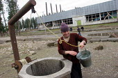A displaced jobless man fetches water in front of a delapitated factory transformed into a center for Georgians who used to live in Abkhazia, Zugdidi, Georgia, March 2005. The region of Abkhazia, offi... - Boris Heger - 08-03-2005