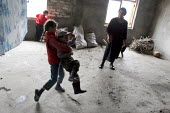 Children play in a delapitated residential block transformed into a displaced persons center for Georgians who used to live in Abkhazia, Zugdidi, Georgia, March 2005. The region of Abkhazia, officiall... - Boris Heger - 08-03-2005