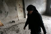 A woman walks in a delapitated residential block transformed into a displaced persons center for Georgians who used to live in Abkhazia, Zugdidi, Georgia, March 2005. The region of Abkhazia, officiall... - Boris Heger - 08-03-2005