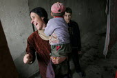 A woman laughs with her child in a delapitated residential block transformed into a displaced persons center for Georgians who used to live in Abkhazia, Zugdidi, Georgia, March 2005. The region of Abk... - Boris Heger - 08-03-2005