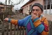A man stands in front of a delapitated residential block transformed into a displaced persons center for Georgians who used to live in Abkhazia, Zugdidi, Georgia, March 2005. The region of Abkhazia, o... - Boris Heger - 08-03-2005