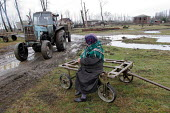 A farmer takes a rest on her wooden cart as a tractor passes by, Chaladidi, Georgia, March 2005. - Boris Heger - 10-03-2005