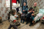 A family stand in their room in a delapitated residential block transformed into a displaced persons center for Georgians who used to live in Abkhazia, Kutaisi, Georgia, March 2005. The region of Abkh... - Boris Heger - 10-03-2005
