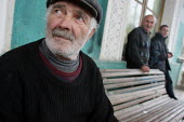 Old men stand in front of an old former official building transformed into a displaced persons center for Georgians who used to live in Abkhazia, Kutaisi, Georgia, March 2005. The region of Abkhazia,... - Boris Heger - 10-03-2005