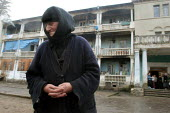 An elderly woman stand in front of an old former official building transformed into a displaced persons center for Georgians who used to live in Abkhazia, Kutaisi, Georgia, March 2005. The region of A... - Boris Heger - 10-03-2005