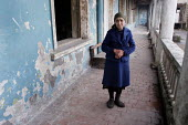 An old woman stands at the entrance of her room in an old former official building transformed into a displaced persons center for Georgians who used to live in Abkhazia, Kutaisi, Georgia, March 2005.... - Boris Heger - 10-03-2005