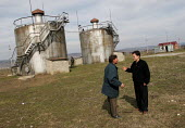An ICRC engineer and a local official talking with each other in front of ICRC-built drinking-water tanks serving a village playing host to many refugees displaced from Chechnya. The tanks are connect... - Boris Heger - 18-03-2005
