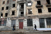 People pass by a building destroyed during the war, Grozny, Chechnya, March 2005. - Boris Heger - 23-03-2005