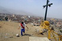 A boy wearing the national teams football strip plays alone in a slum, Lima, Peru, September 2004. - Boris Heger - 29-08-2004