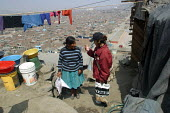 Two women chat in front of their house overlooking the slum where they live, Lima, Peru, September 2004. - Boris Heger - 29-08-2004