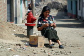 An woman knits in front of her house in a slum, Lima, Peru, September 2004. - Boris Heger - 29-08-2004