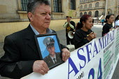 Colombia. A man displays a picture of his son who was kidnapped by a guerilla group, as Marteny Orjuela Manjarres, background, President of the association ASFAMIPAZ (the organisation of relatives of... - Boris Heger - 20-02-2007