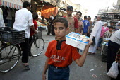 A refugee child selling tea in the street to support his family passes by in this area densely populated with Iraqi refugees. There is an estimated 1.4 million Iraqis who sought refuge in Syria due to... - Morris Bernard - 2000s,2007,Arab,Arabs,boy,boys,child,Child Labor,child labour,CHILDHOOD,children,cities,city,communities,community,Diaspora,displaced,earn,Earning,ebf,Economic,economy,employee,employees,Employment,EQ
