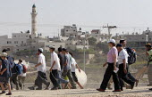 Jewish settlers pass in front of a mosque, while marching from the West Bank settlement of Efrat toward a hill called Eitam, near Bethleem, where they want to establish an outpost settlement. Israeli... - Morris Bernard - 30-09-2007