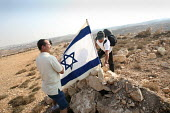 Jewish settlers plant an Israeli flag on a hill called Eitam, near Bethleem, where they want to establish an outpost settlement. Israeli settlers and rightwing groups announced that they would attempt... - Morris Bernard - 30-09-2007