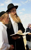A Jewish Orthodox settler and his son pray and read the sacred Torah book on a hill called Eitam, near Bethleem, where they want to establish an outpost settlement. Israeli settlers and rightwing grou... - Morris Bernard - 30-09-2007