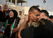 A former Palestinian prisoner, center, is greeted by his brother, a member of Fatah security forces after being released from an Israeli jail. Fifty-seven Palestinian prisoners have been released and... - Morris Bernard - 01-10-2007