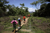 Tule women walking together out into the jungle to collect water and firewood. This village of Indigenous Tule have been displaced by conflict, to the Panama border region of the Darien gap. Their cul... - Boris Heger - 2010,2010s,ACE,americas,Amerindian,Amerindians,border,bridge,bridges,communities,community,conflict,costume,culture,Cuna,darien,Darien Gap,Darien National Park,displaced,displacement,Dule,dulemola,emp