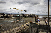Children flying a kite in a slum area of a pier. Coastal communities who live along the Pacific coast near the city of Buenaventura are in threat of displacement due to conflict. Buenaventura, Colombi... - Boris Heger - 03-07-2010