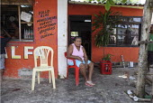 An internally displaced woman sitting in front of her house next to a shop - a general store selling food- in the poor suburb of Pozos Azules, Cartagena. - Boris Heger - 10-11-2010