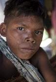 A Nukak Maku indigenous boy from the Amozon rainforest standing in his shelter near San Jose del Guaviare, Colombia. He is one of the last members of his tribe. - Boris Heger - 19-01-2011