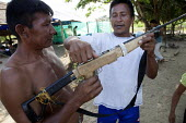 Two internally displaced indigenous men playing with a handmade gun outside their shelter on the outskirts of the city, San Jose del Guaviare, Colombia. - Boris Heger - 20-01-2011