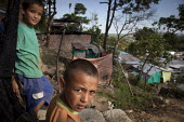 Internally displaced indigenous children standing in front of their shelter in a shantytown in Villavicencio, Colombia. - Boris Heger - 2010s,2011,americas,Amerindian,Amerindians,Barrio,Barrios,boy,boys,child,CHILDHOOD,children,Colombia,Colombian,Colombians,columbian,columbians,communities,community,displaced,displacement,EQUALITY,exc