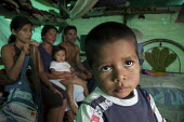 A family of internally displaced indigenous people sitting in their shelter in a shantytown in Villavicencio, Colombia. - Boris Heger - 21-01-2011