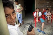Boys playing with a plastic toy gun in a shantytown in Villavicencio, Colombia. - Boris Heger - 2010s,2011,adolescence,adolescent,adolescents,americas,Amerindian,Amerindians,babies,baby,Barrio,Barrios,boy,boys,child,CHILDHOOD,children,Colombia,Colombian,Colombians,columbian,columbians,communitie