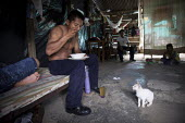 An internally displaced indigenous man who works in a supermarket having a meal at home after a long day at work, watched by a kitten, in a poor neighbourhood in Villavicencio, Colombia. - Boris Heger - 22-01-2011