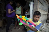 An internally displaced indigenous boy playing with a gun made of Lego Duplo bricks in a poor neighbourhood in Villavicencio, Colombia. - Boris Heger - 22-01-2011