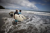 Young surf champion PJ walking into the waves with his friend. Choco, Colombia. - Boris Heger - 13-08-2011