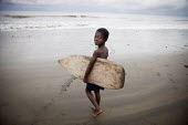 A young surfer heading to the water with a surfboard his older brother made for him from a balsa tree in the jungle. Choco, Colombia. - Boris Heger - 14-08-2011