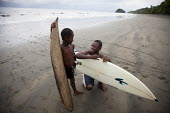 The young surf champion PJ and his brother discussing how to catch the best waves before heading into the water. Choco, Colombia. - Boris Heger - 2010s,2011,adolescence,adolescent,adolescents,Afro,Afro Colombians,afro-descendants,americas,BAME,BAMEs,beach,beaches,Black,BME,bmes,board,boards,boy,boys,catch,child,CHILDHOOD,children,class,coast,co