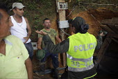 Police officers talk to distraught miners- has just lost everything as his illegal mine has been closed down by police officers. The Colombian government says it wants to control illegal mining and is... - Boris Heger - 11-03-2012