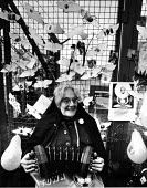 Veteran Peace campaigner Angela Gradwell playing her concertina USAF Greenham Common Cruise Missile base, 1982 - Bob Naylor - 1980s,1982,activist,activists,against,age,ageing population,airforce,American,americans,anti,Anti Nuclear weapons,Anti War,Antiwar,Armed Forces,CAMPAIGN,campaign for nuclear disarmament,campaigner,cam