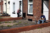 Feraz sits in his front garden enjoying the sun and smoking Shisha while his next door neighbour tends to her garden In Belle Vue Wakefield. Belle Vue is a deprived area of Wakefield with a high Pakis... - Connor Matheson - 28-03-2012