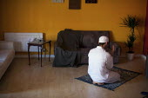 A Palestinian muslim man prays in his flat, Upperthorpe, Sheffield. Upperthorpe has a big Arabic community. - Connor Matheson - 30-03-2012