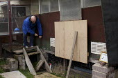 A Pigeon fancier locks away his back garden pigeon loft after preparing them for a race the next day. He is a welder but has been racing pigeons with his brother since they were children. Woodthorpe,... - Connor Matheson - 13-04-2012