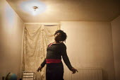 An unemployed resident of the park hill estate in her flat, Sheffield - Connor Matheson - 2010s,2013,BAME,BAMEs,Black,BME,bmes,cannabis,CIGARETTE,cigarettes,cities,city,council estate,council services,council estate,council services,deprivation,diversity,drug,drugs,EQUALITY,ethnic,ethnicit