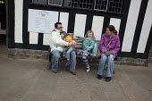 A family visiting Stratford-upon-Avon sitting outside the public library, Warwickshire - Connor Matheson - 2010s,2013,boy,boys,child,CHILDHOOD,children,DAD,DADDIES,DADDY,DADS,elizabethan,families,family,father,FATHERHOOD,fathers,female,females,girl,girls,holiday,holiday maker,holiday makers,holidaymaker,ho