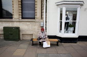 A woman visiting Stratford-upon-Avon sitting outside a clothes shop, Warwickshire - Connor Matheson - 09-04-2013