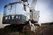 A young man rolling a Cigarette sitting on a derelict crane, Rotherham - Connor Matheson - 26-04-2014