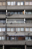 A man smokes on his balcony at the Aylesbury estate, London. - Connor Matheson - 06-02-2012